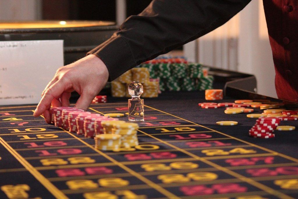Croupier im Casino stellt Spielchips auf das Feld.